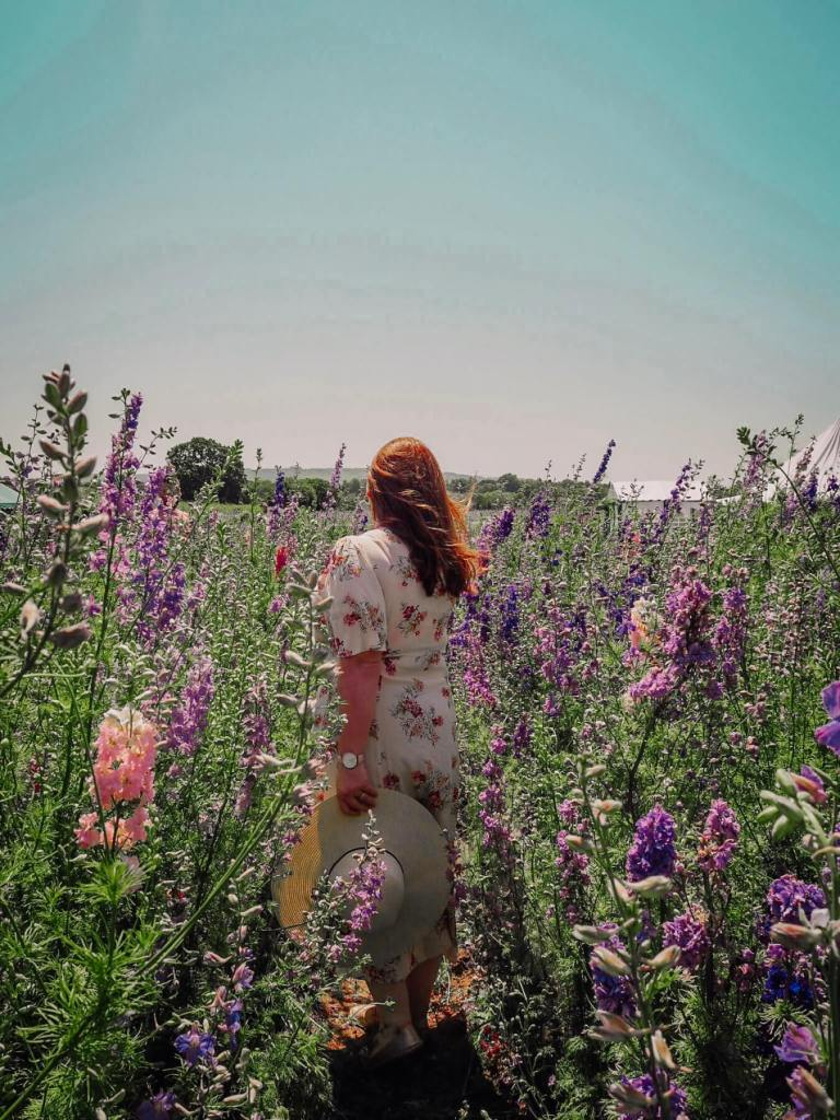 Woman with red hair standing in a flower field