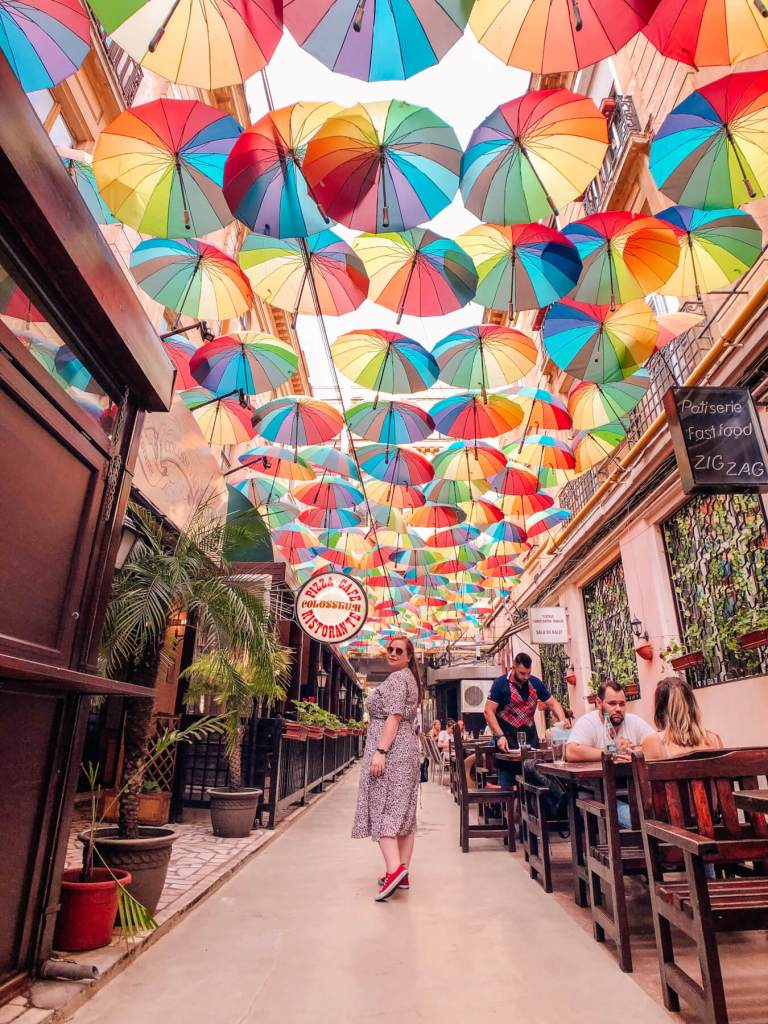 Woman standing under a colourful Umbrella sky in Bucharest. The best travel hashtags to use for killer reach. A list of over 250 travel hashtags for Instagram. Read more on www.allaboutrosalilla.com