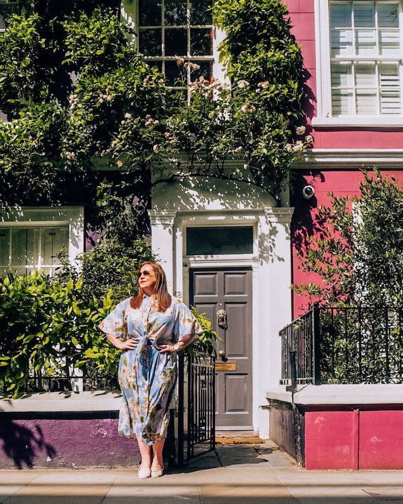 Woman in a blue floral dress posing in front of the pastel coloured houses of Notting Hill London