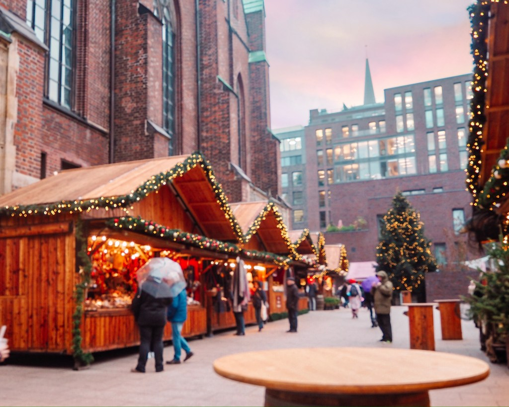 Rustic wooden huts with fairy lights at the St Petri Christmas markets