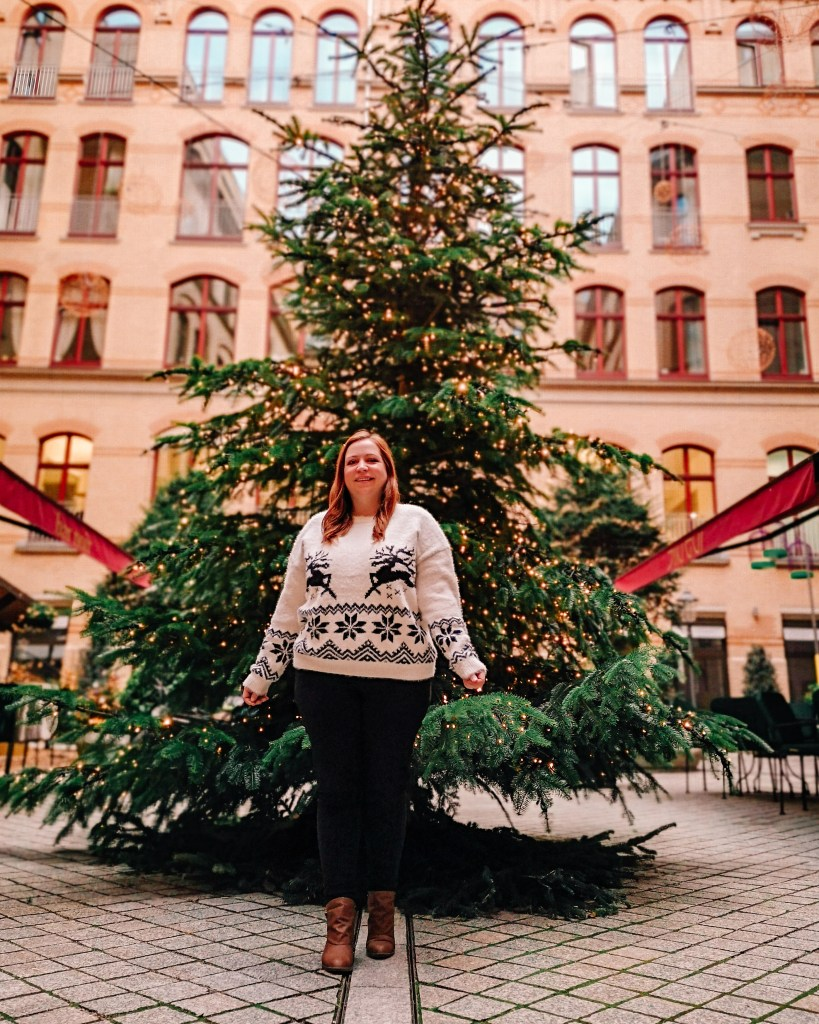Girl standing in front of a Christmas tree wearing a Christmas jumper