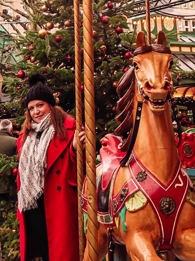 Girl in red coat at carousel at Hamburg Christmas Markets