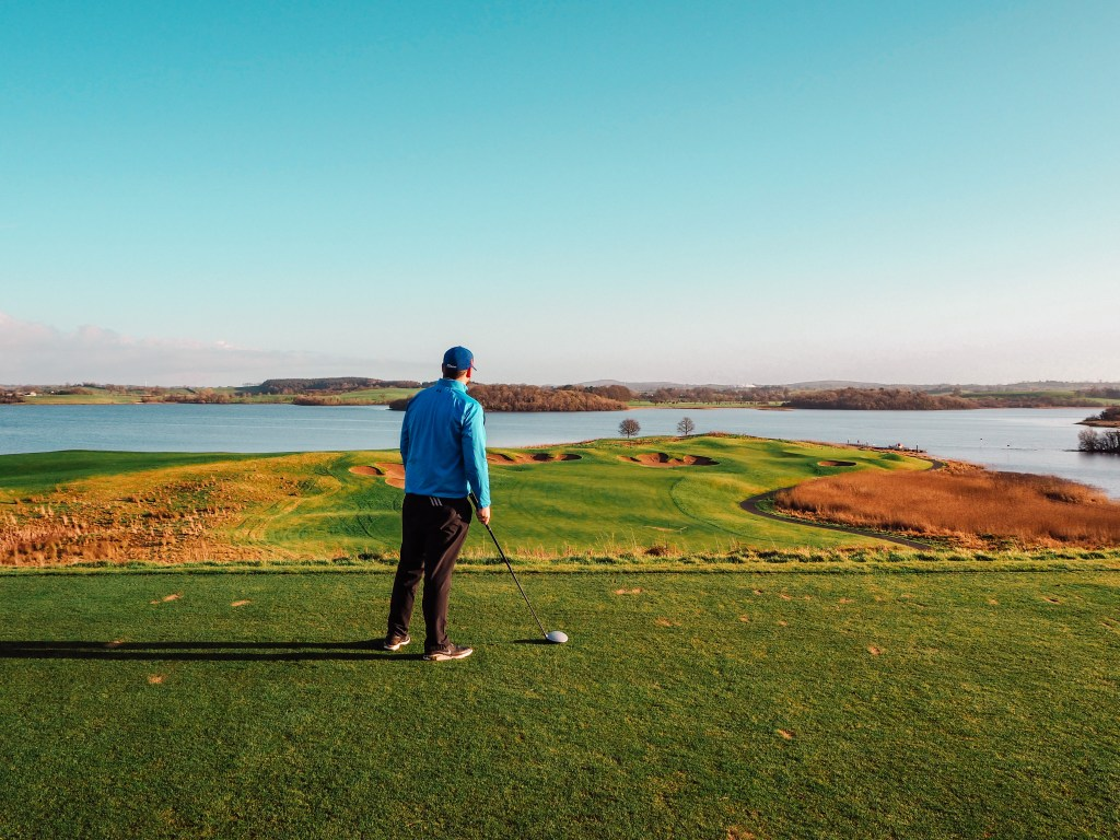 Male golfer in a blue top and black pants holding a golf club and admiring the views from hole 7 at Lough Erne resort.