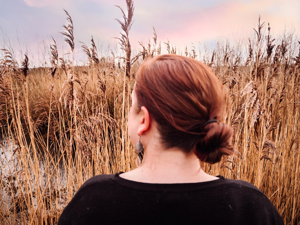Woman wearing her red hair in a loose bun looking out over the reeds of Castle Hume Lough in Northern Ireland.