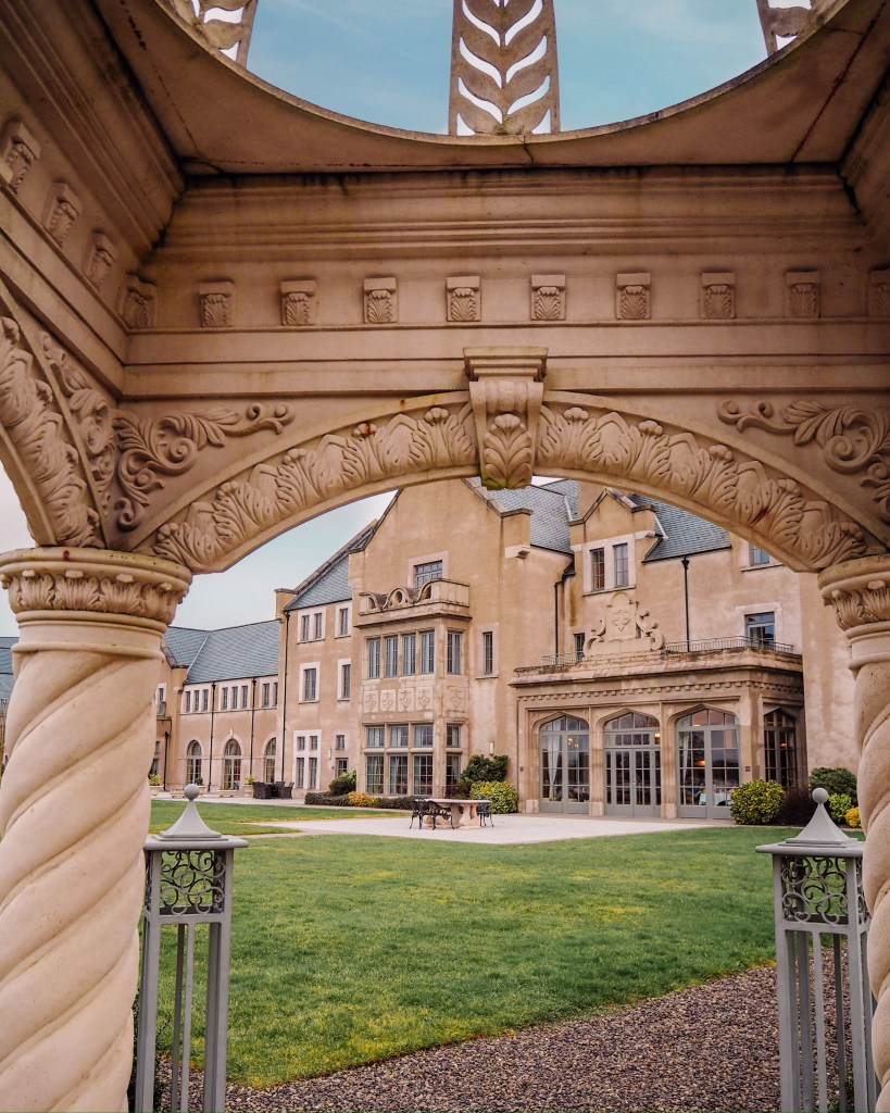 Country Manor house style of the main hotel building of Lough Erne viewed through the archway of an ornate gazebo on the grounds of the hotel.