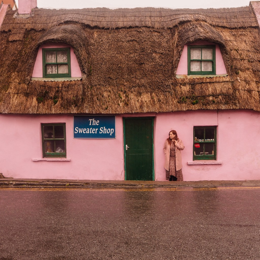 Irish woman in a pink coat resting against a pink thatch cottage in Doolin County Clare Ireland