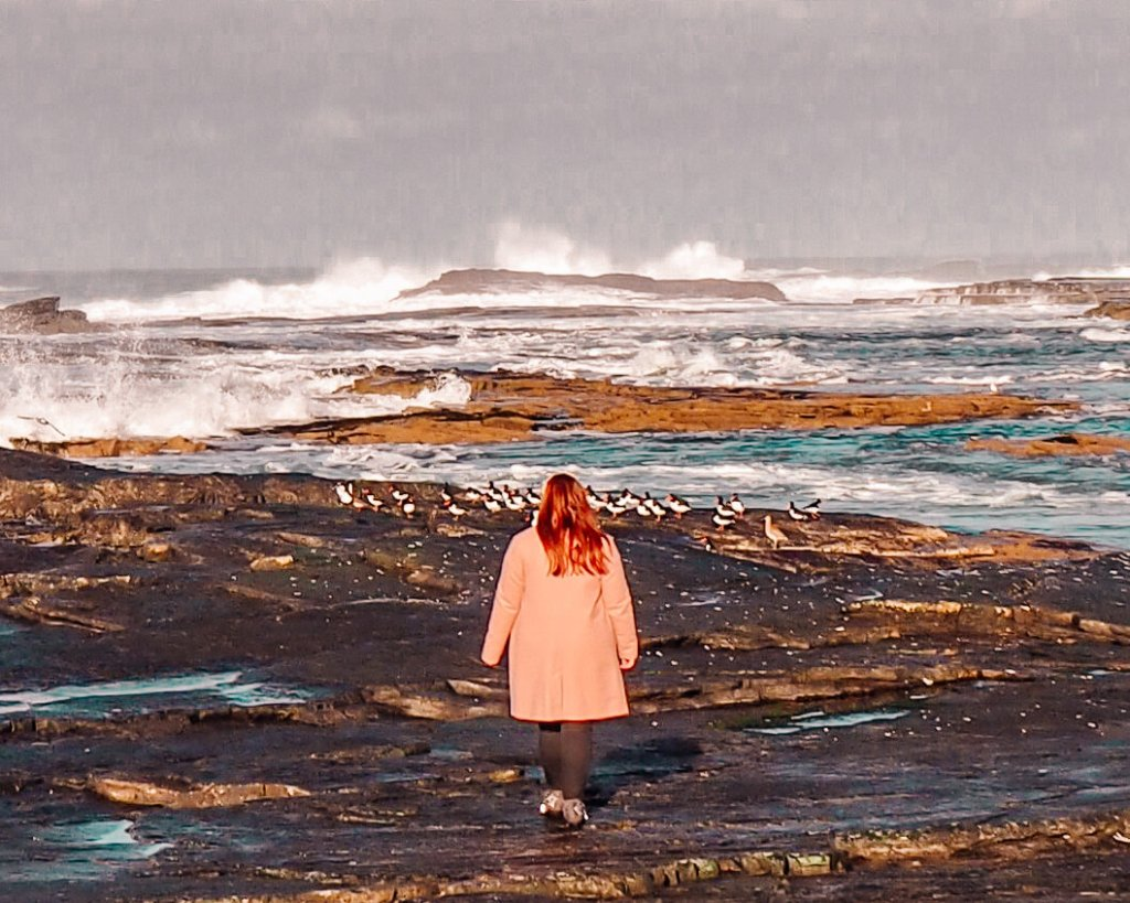 Irish woman with red hair wearing a pink coat and walking along a stony beach in Kilkee County Clare Ireland.
