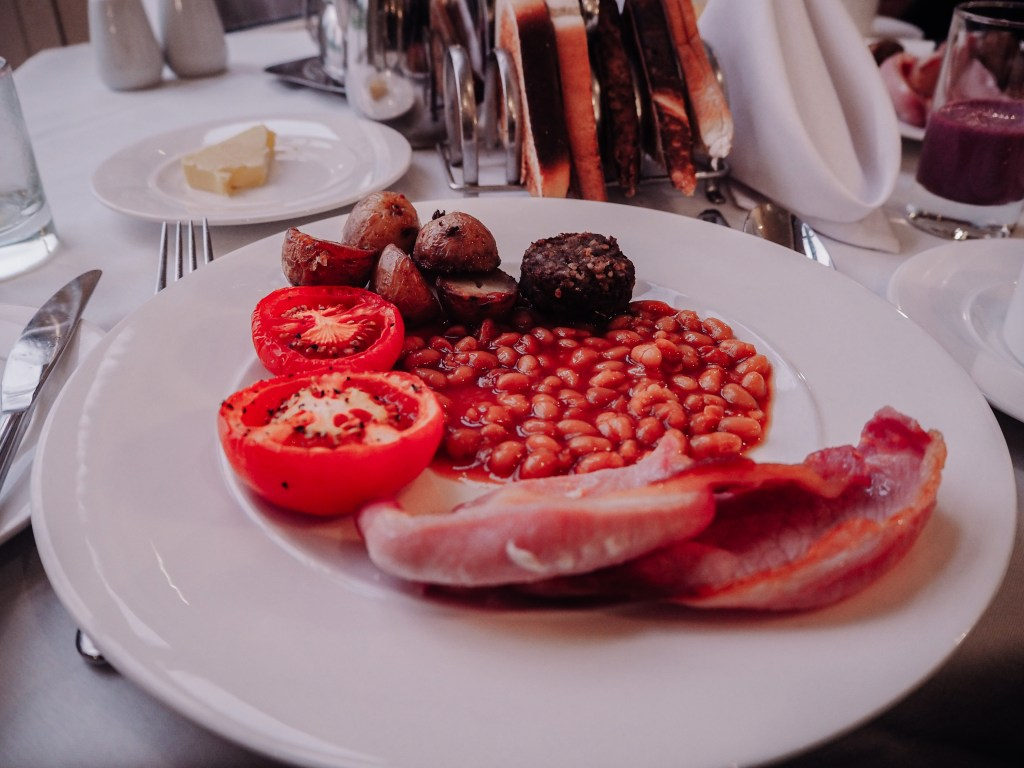 Irish breakfast with rashers, beans, tomatoes and white pudding on a plate.