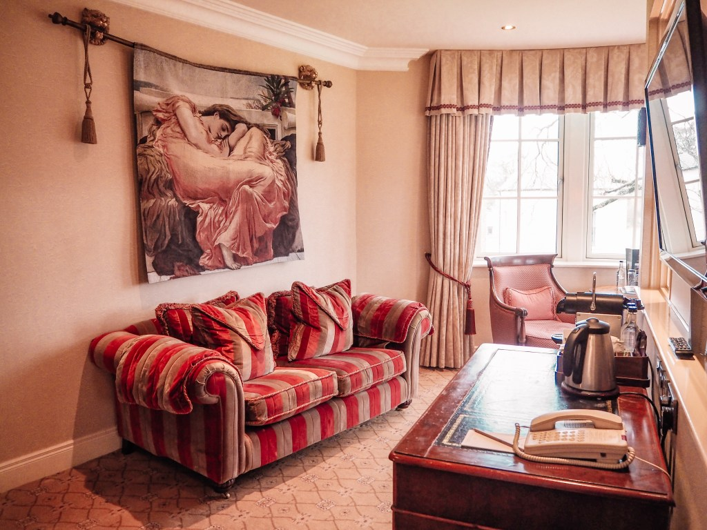 The seating area of the Dovecote suite in Lough Erne resort with a plush velvet red and beige couch and a tapestry of a woman in a pink dress on the wall.