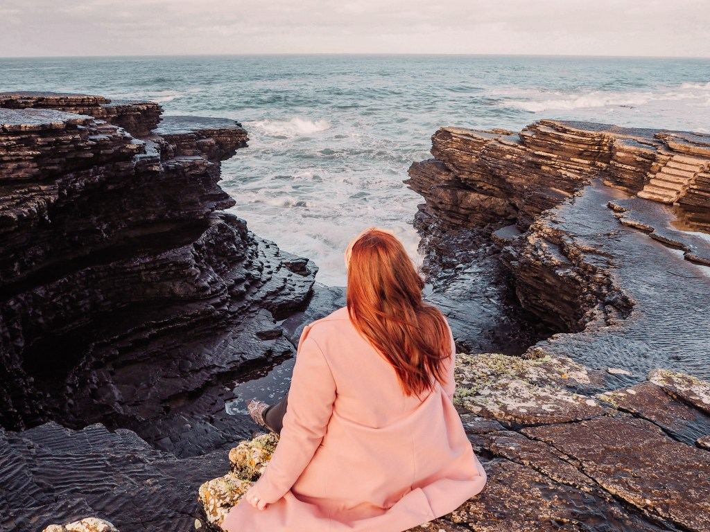 Irish woman with red hair and wearing a pink coat sitting at the cliffs edge at Kilkee Cliffs In County Clare Ireland
