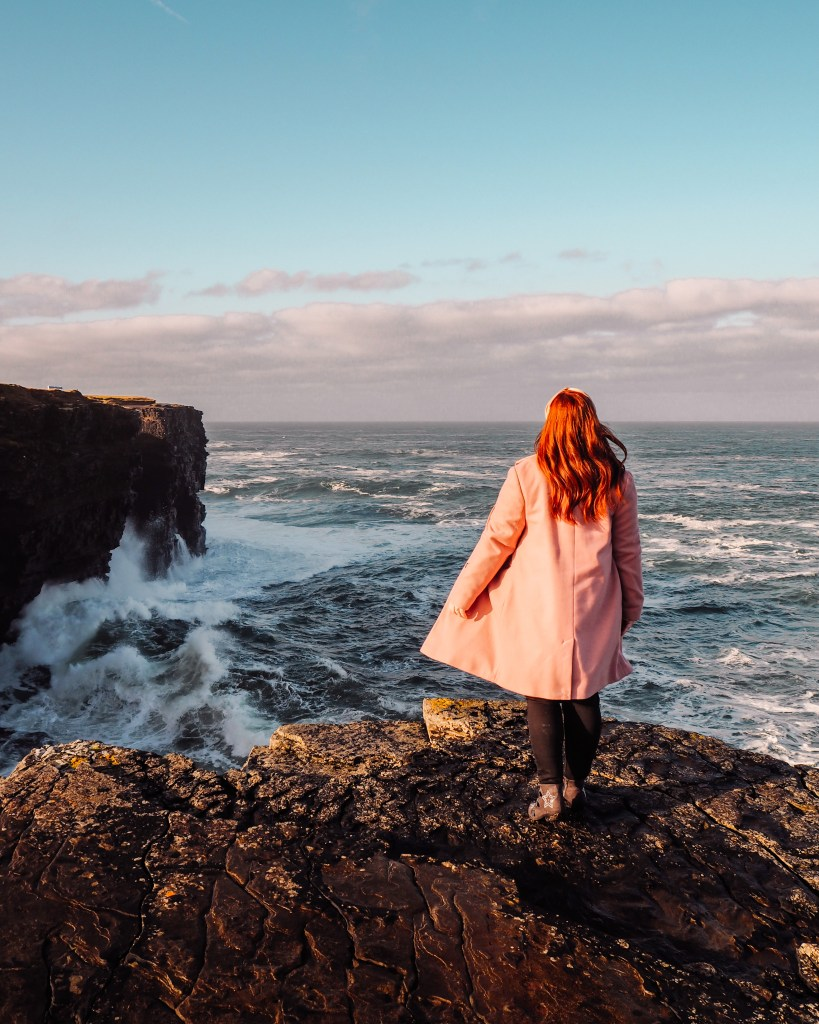 Irish woman with red hair and wearing a pink coat looking out at the wild Atlantic ocean in Ireland.