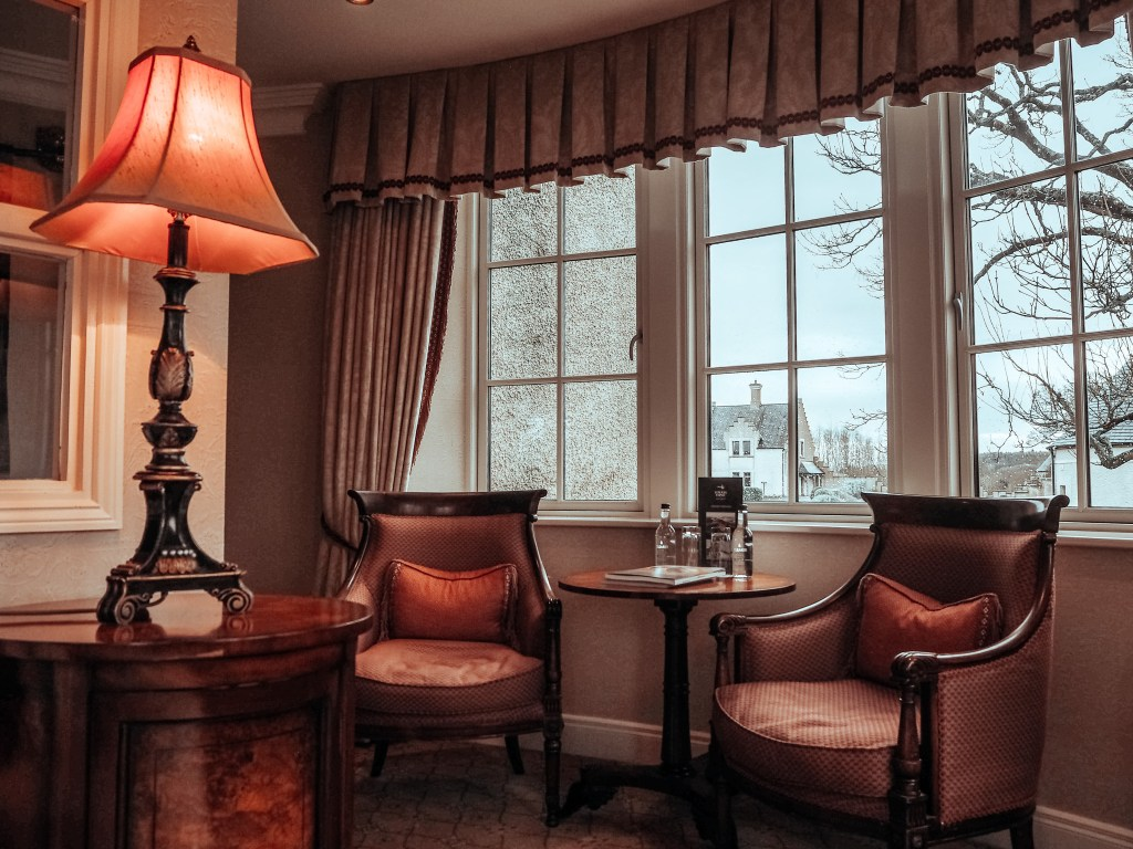 Corner of The Dovecote suite at Lough Erne resort with a seated area containing two armchairs and a reading lamp.