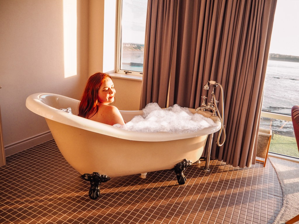 Woman enjoying a bubbl bath at sunset in a luxury hotel in Ireland