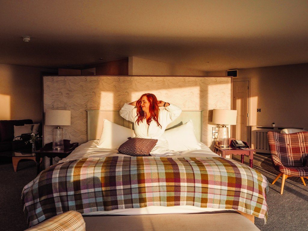 Woman stretching in a hotel bed at Armada Spanish Point Hotel Ireland