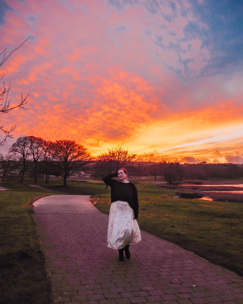 Woman with red hair and wearing a silver sequin skirt walking along the lakeshore of one of Ireland's most luxurious and romantic hotels at sunset.