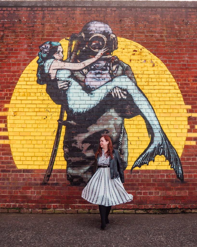 Woman wearing a leather jacket and white dress standing infront of a mural of a deep sea diver carrying a mermaid.