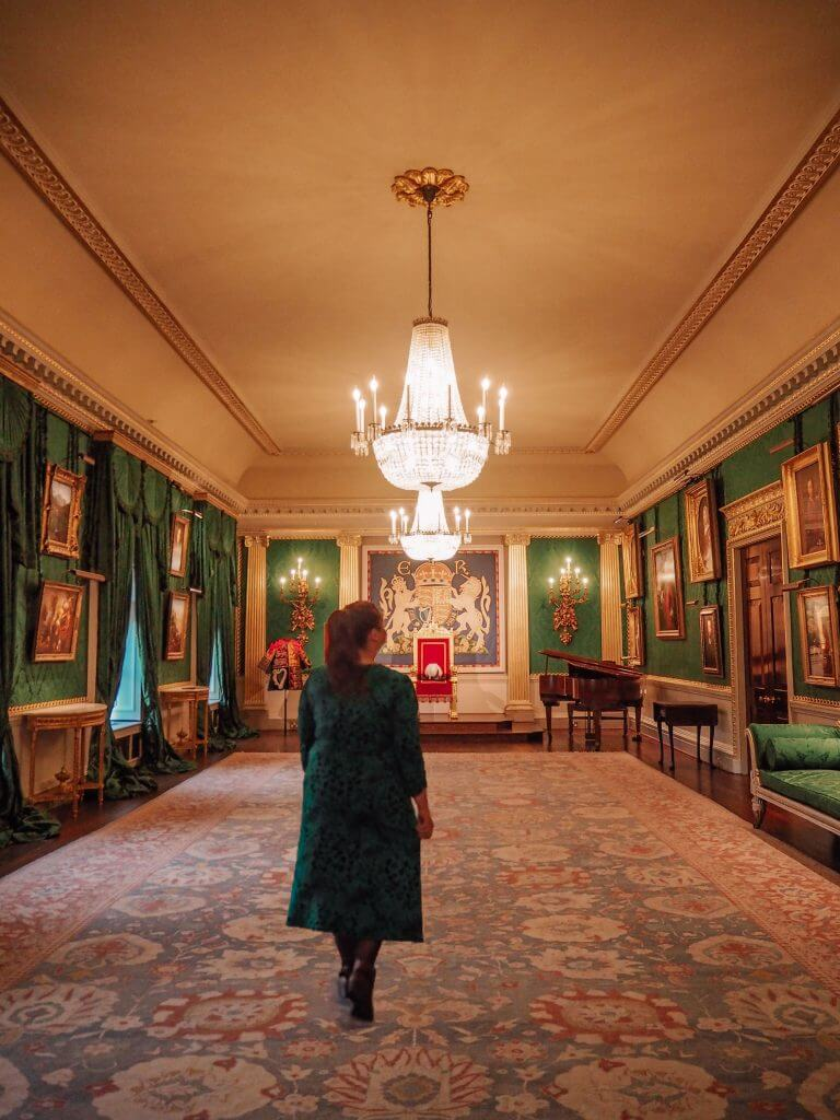 Woman in a green dress walking in the throne room of Hillsborough Castle in Northern Ireland