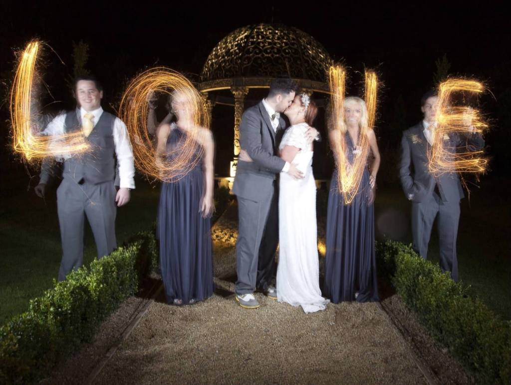 Couple on their wedding day surrounded by sparklers that spell the word Love
