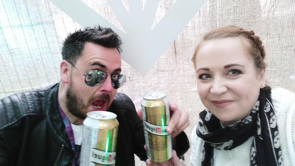 Couple drinking a can of beer at a music festival