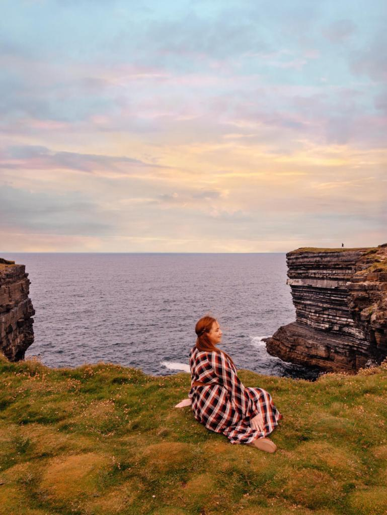 Woman in a tartan dress sitting at the cliffs of Downpatrick Head Mayo
