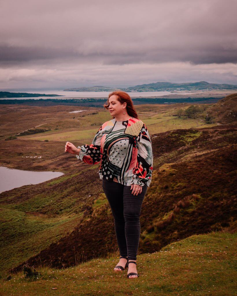 Woman in a colourful top overlooking the views of the Wild Atlantic Way in Donegal
