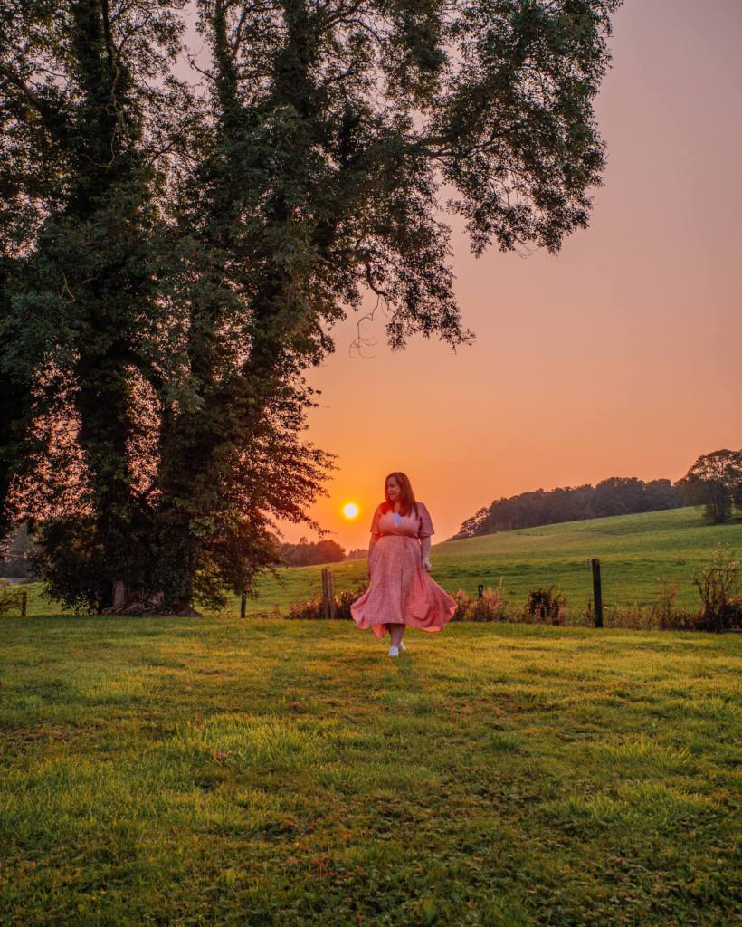 Woman in a red dress walking in the gardens of Loughcrew Lodge at sunset on a unique Irish staycation