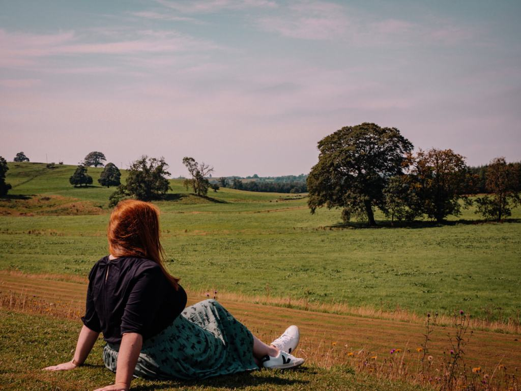 Woman sitting on the grass and enjoying the views at Loughcrew Estateand gardens a wonderful thing to do in County Meath Ireland