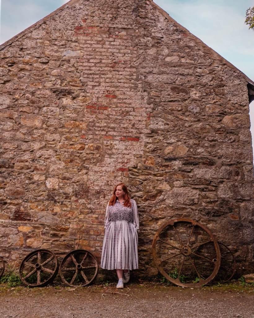 Woman standing against a barn at Greenan Maze in Wicklow Ireland on her staycation Ireland