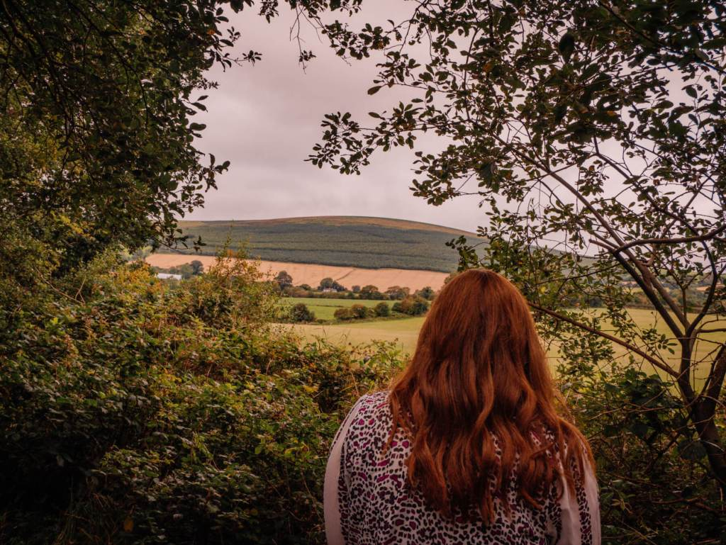 Woman with red hair looking out at a view of the Wicklow mountains from the Railway walk in Tinahely Ireland.