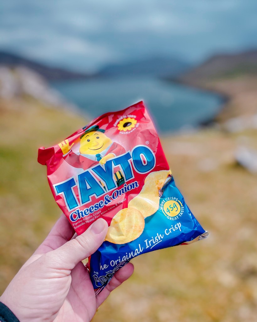Hand holding up a bag of Tayto on a Connemara hike