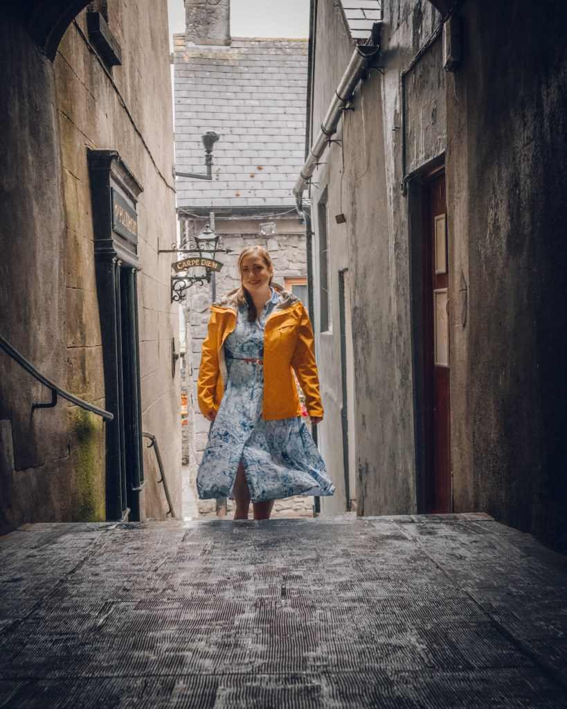 Woman in a yellow raincoat walking through the medieval streets of Kilkenny Ireland
