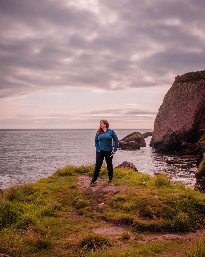 Woman wearing black trousers and a blue top exploring the Antrim coastline