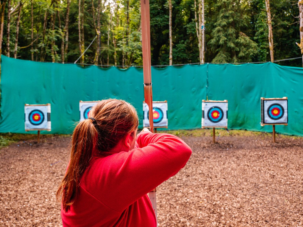 Woman trying archery at Castlecomer Discovery Park in Kilkenny Ireland