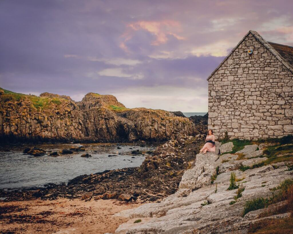 Woman in a pink dress sitting on the rocks at Ballintoy Harbour in County Antrim