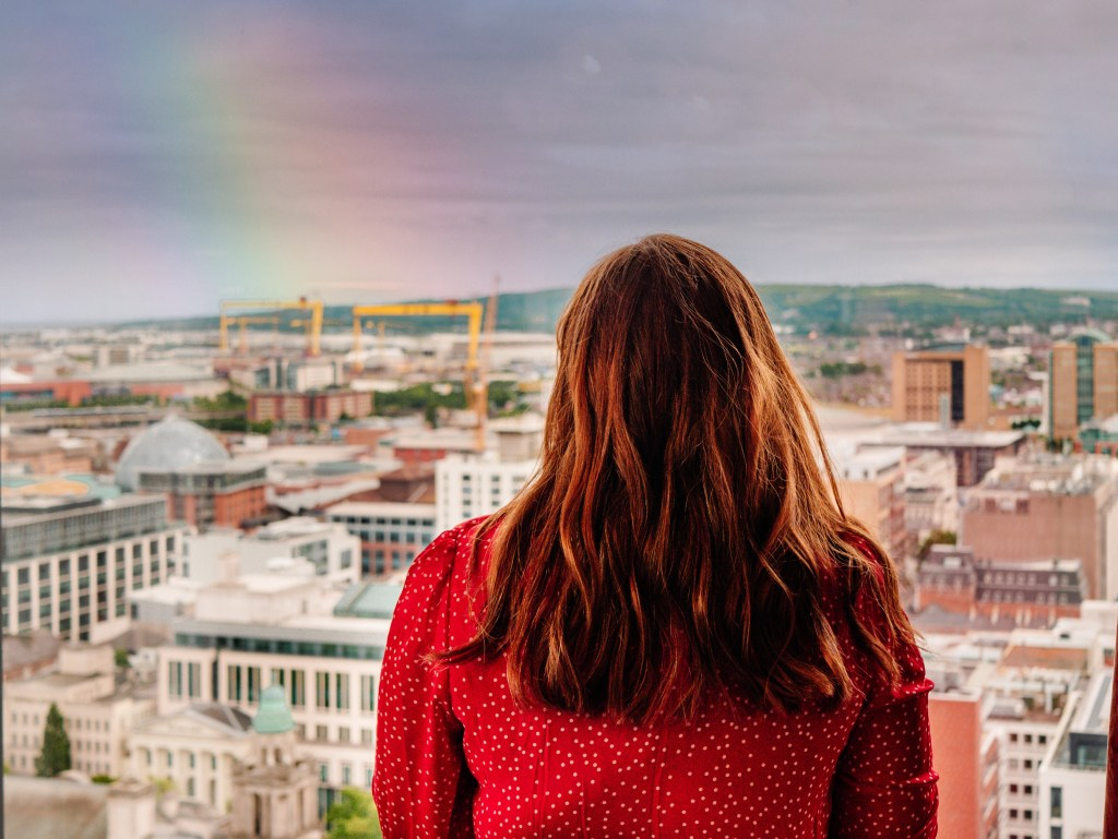 Woman in a red dress looking at the views of Belfast city from the Observatory Bar in The grand central hotel Belfast