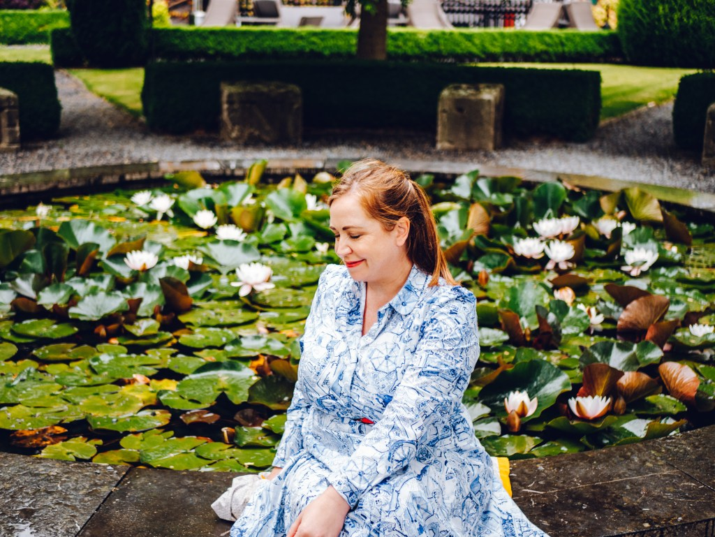 Woman in a blue dress sitting at a lily pond in Butler House Kilkenny