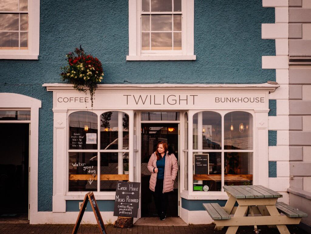 Woman in a pink coat standing in the doorway of Twilight cafe in Carlough Harbour a game of thrones Ireland filming location