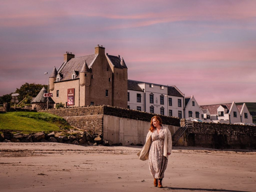 Woman walking on the beach at sunset ay Ballygally Castle Hotel in Northern Ireland