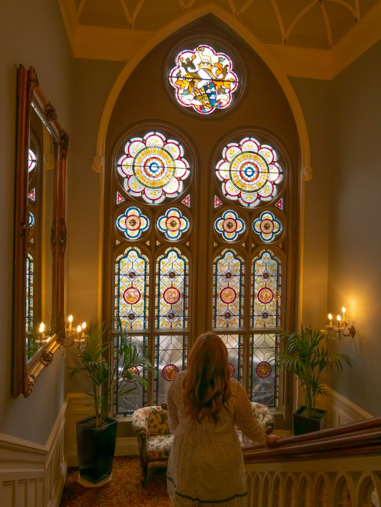 Woman looking at a stain glass window on the staircase of the Culloden Estate and Spa