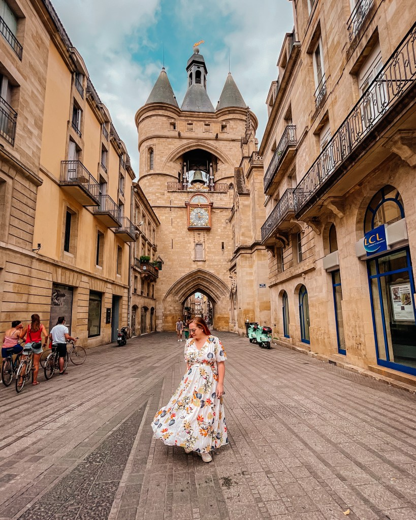 Woman in a floral dress walking in front of the Grosse cloche in Bordeaux France