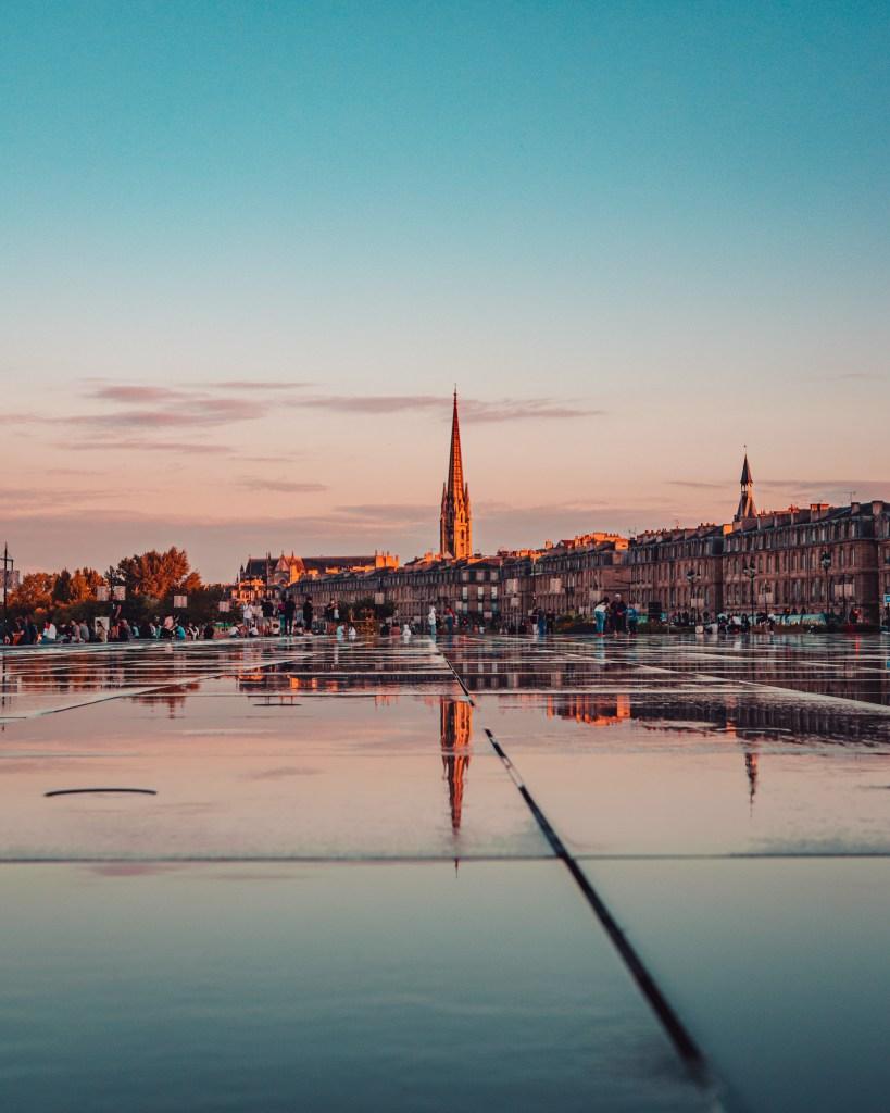 Reflection of a church steeple in Miroir d'eau one of the best Instagram spots in Bordeaux