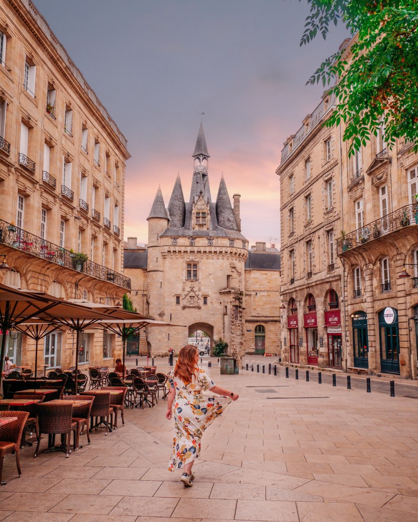 Woman standing in front of Porte Cailhau one of the best Instagram spots in Bordeaux