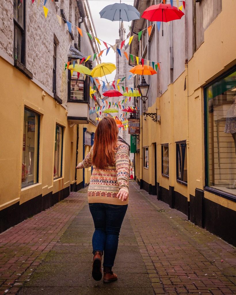 Woman walking under an umbrella sky on a weekend break in Galway Ireland
