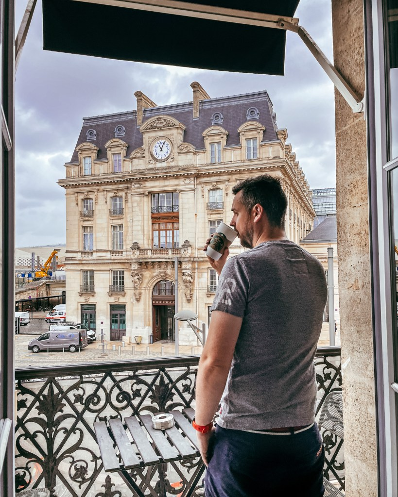 Man drinking coffee with a view of Gare St Jean train station on a 2 day Bordeaux itinerary