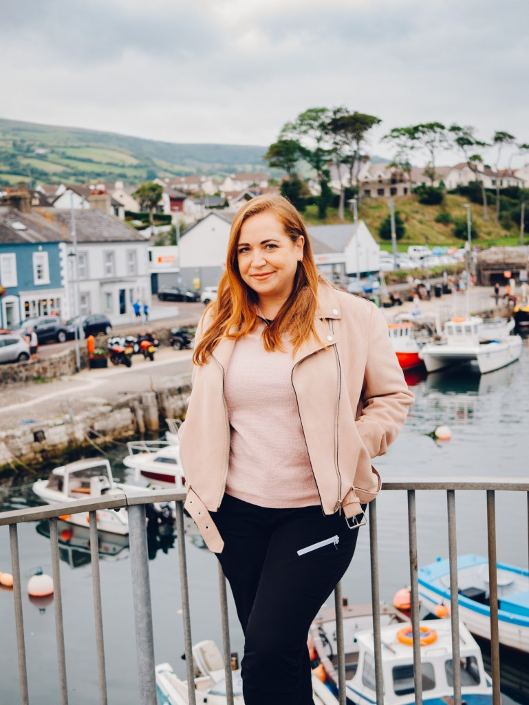 Woman standing at Carnlough Harbour in County Antrim