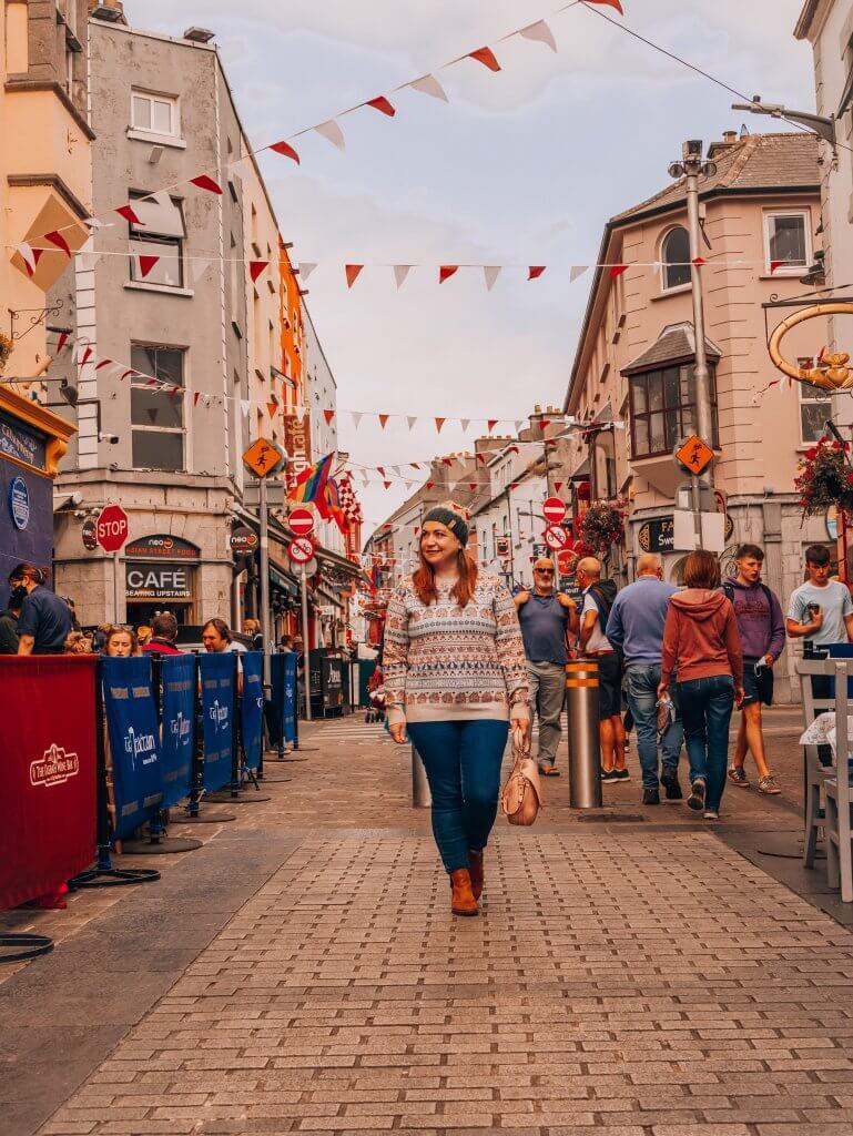 Woman walking along the Latin Quarter on a weekend break in Galway city Ireland