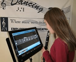 A photo of a young girl playing a flute and reading enlarged musical notes from a special device enlarging images.