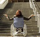 A photo of a woman from the back of unknown age in a wheelchair; the woman spreads out her arms in show of desperation. In front of the woman are steep and long stairs, the end of the stairs are not visible.