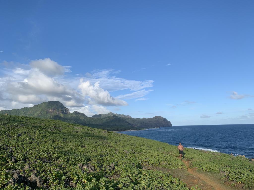Joe Bauer running on a coastal trail in Poipu with beautiful coastal view