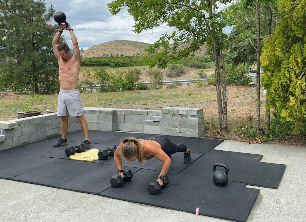 Joe doing kettlebell swings and Emily doing push-ups